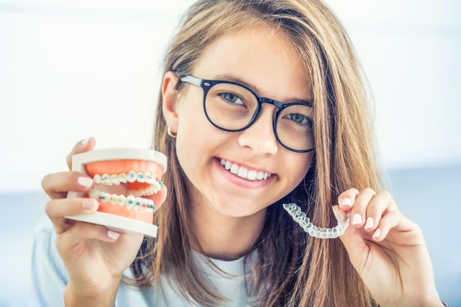 smiling young lady holding invisible braces and a silicone trainer in each hand